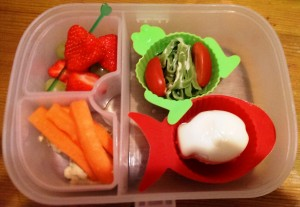 Fish-shaped egg (using egg mold) in fish silicome cup, spinach pasta and tomatoes in frog silicone cup, carrot sticks and houmus with strawberries and green heart pick.